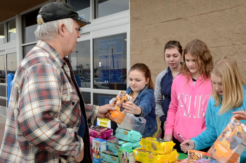 Girls sell Girl Scout Cookies to a man at a cookie booth sale.